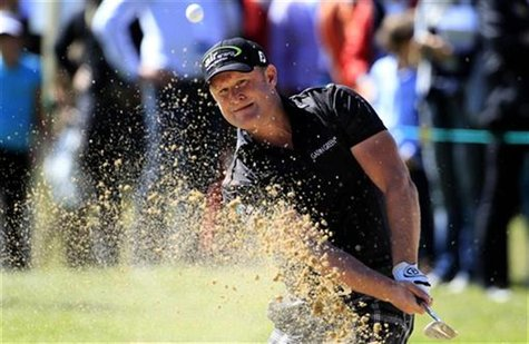Jamie Donaldson of Wales hits out of a bunker onto the 15th green during the final round of the European Masters golf tournament in the Swis