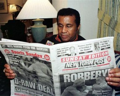 Noted boxing trainer Emanuel Steward reads the Sunday tabloids in New York in this March 14, 1999 file photo. REUTERS/Teddy Blackburn