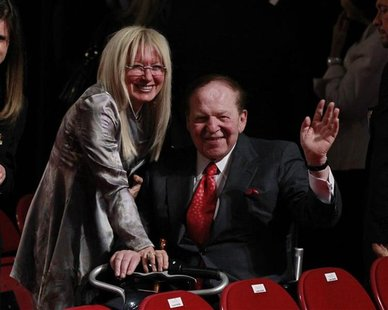 Chairman and CEO of the Las Vegas Sands casino Sheldon Adelson (C), a donor to Republican presidential nominee Mitt Romney, waves to photogr