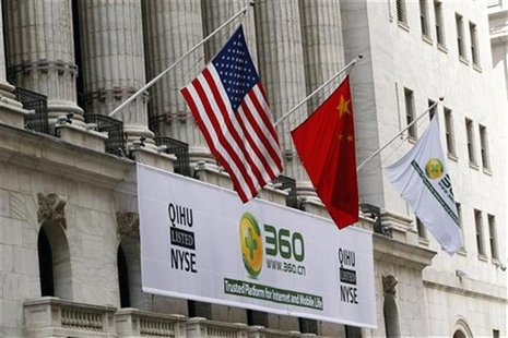 A sign advertising the Qihoo 360 Technology Co Ltd is hung with the U.S. and Chinese flags outside of the New York Stock Exchange before the