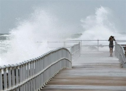 Jean Marie Brennan walks along the jetty at Lighthouse Point Park as Hurricane Sandy passes offshore in Ponce Inlet, Florida, October 26, 20