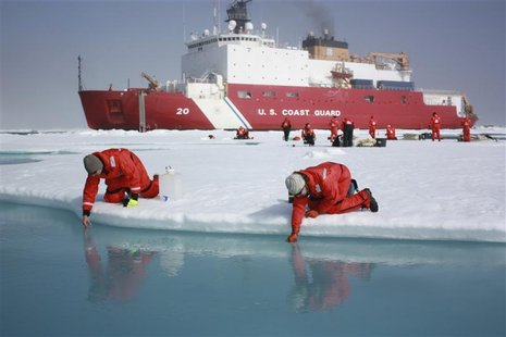 Scientists Jens Ehn (L) and Christie Wood scoop water from melt ponds on sea ice in the Chukchi Sea in the Arctic Ocean in this July 10, 201