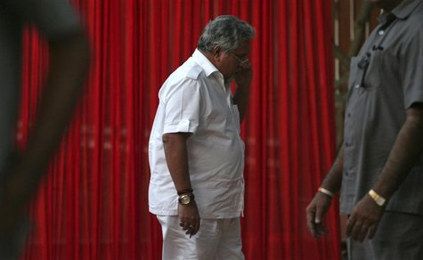 Kingfisher Airlines Chairman Vijay Mallya speaks on a mobile phone amid his security personnel on guard during a meeting with the debt-laden