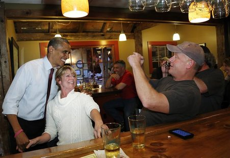 President Barack Obama (L) mingles in the bar with diners at the Common Man restaurant in Merrimack, New Hampshire October 27, 2012. REUTERS