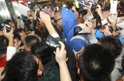 Fans take photos of former NBA player Tracy McGrady as he arrives at Qingdao airport, Shandong province October 24, 2012. REUTERS/China Dail