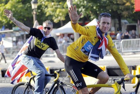 Sky Procycling rider and leader's yellow jersey Bradley Wiggins of Britain and Sky Procycling Sport director Sean Yates (L) celebrate with B