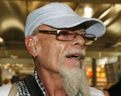 British rocker Gary Glitter walks at Bangkok's Suvarnabhumi Airport August 20, 2008. Glitter was stuck at Bangkok airport on Wednesday after faking illness to avoid boarding a flight to Britain following his release from a Vietnamese prison for child sex abuse, Thai police said. The 64-year-old Briton, whose real name is Paul Gadd, flew to Bangkok after being booted out of the communist southeast Asian country on Tuesday, the day he completed his three-year sentence. REUTERS/Sukree Sukplang