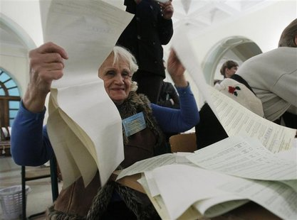 A member of a local electoral commission counts ballots at a polling station after voting day in Kiev October 28, 2012. REUTERS/Gleb Garanic