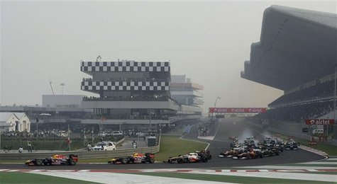 Red Bull Formula One driver Sebastian Vettel (L) of Germany leads on the first turn of the Indian F1 Grand Prix at the Buddh International C