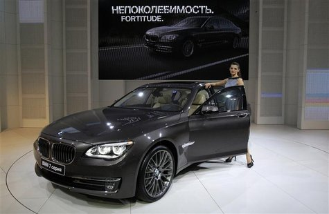 A model stands next to a BMW 7 series car during preparations for the Moscow International Automobile Salon August 29, 2012. REUTERS/Sergei