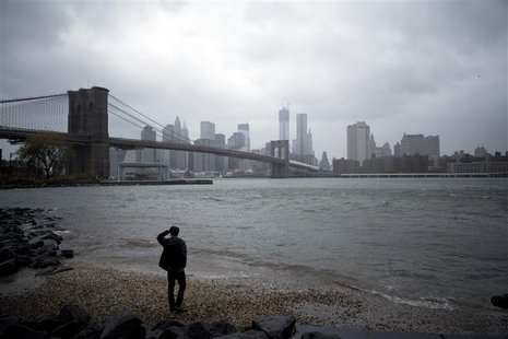 A man watches rising waters on the East River from Brooklyn as Hurricane Sandy made its approach in New York October 29, 2012. REUTERS/Andre