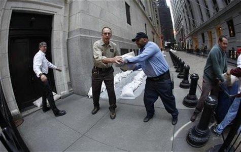 New York Stock Exchange workers place sand bags in front of doors and over electrical vaults at the exchange in New York October 28, 2012. R