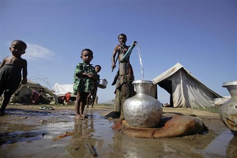 People collect water at a refugee camp for Muslims displaced by violence earlier this year outside Sittwe October 30, 2012. REUTERS/Soe Zeya