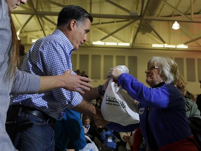 U.S. Republican presidential nominee Mitt Romney accepts relief supplies for people affected by Hurricane Sandy at a storm relief campaign e