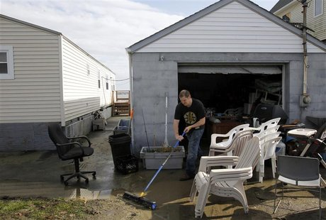Mike Starkie sweeps mud out of his garage as he cleans up from Hurricane Sandy in Fairhaven, Massachusetts October 30, 2012. REUTERS/Jessica
