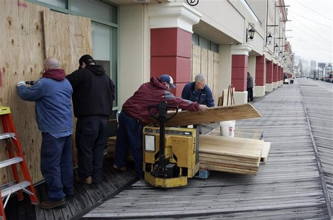 A crew from the Tropicana Casino removes plywood sheets from the windows facing the ocean on the boardwalk following the aftermath of Hurric