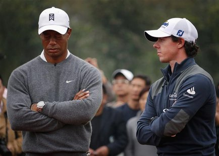 Tiger Woods (L) of the U.S. reacts as he stands next to fellow golfer Rory McIlroy of Northern Ireland during the trophy presentation after