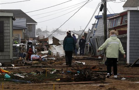 People survey the cottages along Roy Carpenter's Beach that were damaged by Hurricane Sandy in Matunuck, Rhode Island October 30, 2012. REUT