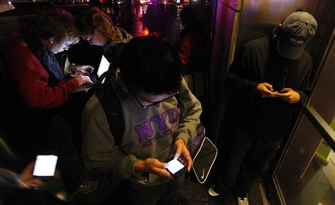People congregate in front of a building that still has wireless internet access in the aftermath of Hurricane Sandy in New York October 30,
