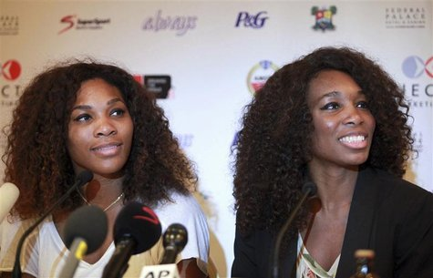 U.S tennis players Serena Williams (L) and Venus Williams smile during a news conference in Nigeria's commercial capital Lagos October 31, 2