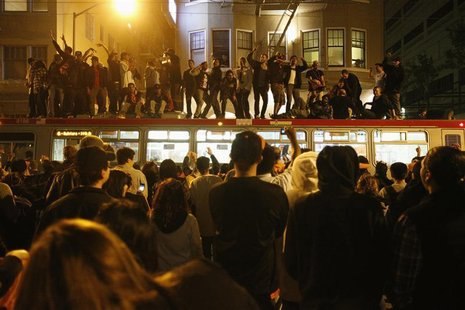 Baseball fans jump on a bus in celebration at Civic Center Plaza after the San Francisco Giants defeated the Detroit Tigers, winning the MLB