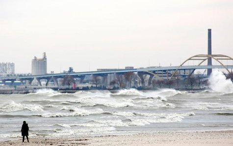 A woman walks along the beach as large surf batters the Milwaukee coastline, a far-reaching effect of Hurricane Sandy, in Wisconsin October 30, 2012. After Hurricane Sandy made landfall on Monday night, Lake Michigan and the other Great Lakes have felt the effects of the storm with high winds and massive surf. REUTERS/Darren Hauck (UNITED STATES - Tags: ENVIRONMENT SOCIETY DISASTER)