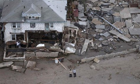 Men stand near a destroyed home in Seagate, New York on October 31, 2012. REUTERS/Adrees Latif