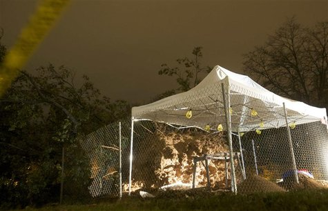 A tent protects the skeletal remains of at least two individuals which were unearthed when a 100-year-old oak tree fell on the Green in New