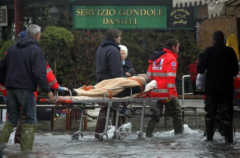 Nurses carry a man on a stretcher in a flooded street during a period of seasonal high water in Venice November 1, 2012. REUTERS/Manuel Silv