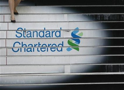 A woman walks down the stairs of the Standard Chartered headquarters in Hong Kong in this October 13, 2010 file photo. Picture taken October