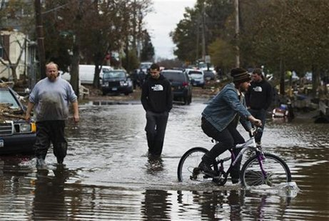 A man rides a bike past three others walking through water still sitting in the streets to survey damage from Hurricane Sandy in the New Dor
