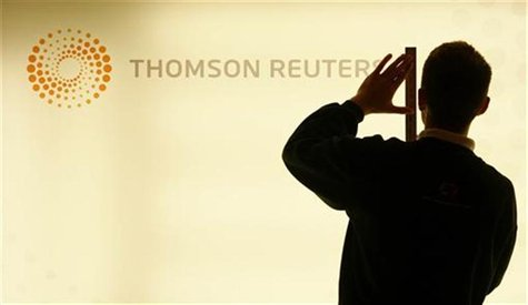 A worker unveils a lightbox displaying the new logo on a Thomson Reuters screen at their headquarters in London's Canary Wharf district earl