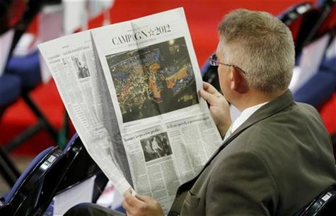 A man on the floor of the convention reads The Washington Post before the start of the second session of the Republican National Convention