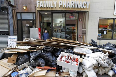 A woman leaves a pharmacy damaged by floodwaters as debris is pilled in the streets in Hoboken, New Jersey, November 2, 2012. REUTERS/Gary H