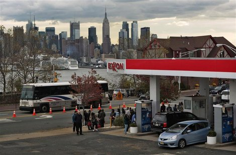 People wait in line to buy gas at a station, as the Empire State Building and the skyline of New York is seen in the background, at Union Ci