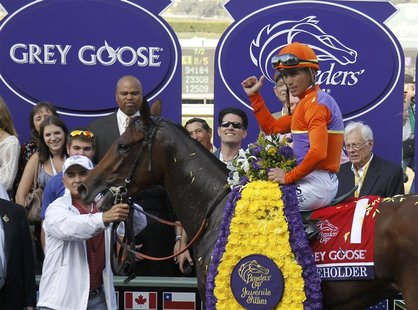 Jockey Garrett Gomez, atop Beholder, celebrates in the winner's circle after the running of the Breeders' Cup Grey Goose Juvenile Fillies th