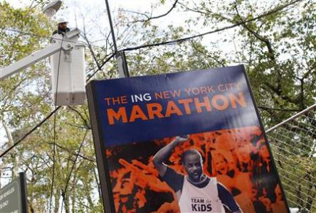 A worker is seen in a bucket truck in front of a sign for the New York City Marathon in the aftermath of Hurricane Sandy in New York November 2, 2012. REUTERS/Carlo Allegri