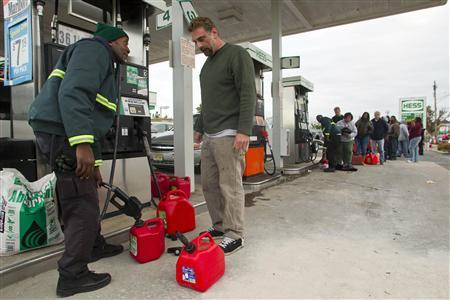 Ovid Thompson (L) fills gasoline cans at a gas station for Bill Poland so he can fuel his car and generator in Neptune, New Jersey, November 2, 2012 in the aftermath of Hurricane Sandy. Credit: REUTERS/Tom Mihalek