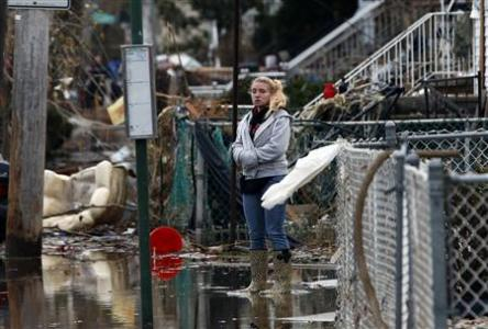 A woman stands alone in water in front of destroyed homes on Cedar Grove Avenue in a neighborhood where many houses were heavily damaged or completely destroyed by storm surge flooding from Hurricane Sandy on the south side of the Staten Island section of New York City, November 1, 2012.
