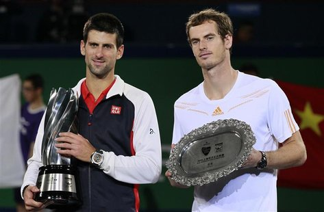 Novak Djokovic (L) of Serbia stands next to Andy Murray of Britain during the trophy presentation after their men's singles final at the Sha