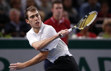 Jerzy Janowicz of Poland returns the ball during his semi-final men's singles match against Gilles Simon of France at the Paris Masters tenn