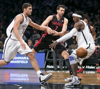 Toronto Raptors center Andrea Bargnani (7) tries to pass between Brooklyn Nets center Brook Lopez (L) and forward Gerald Wallace (R) in the
