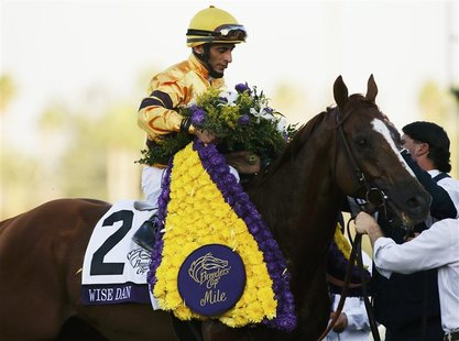 Jockey John Velazquez celebrates aboard horse Wise Dan after his first place win in the running of the Breeders' Cup Mile thoroughbred horse