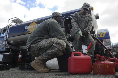 Army Sgt. Adama Ilbouda (L) with the New York Army National Guard, and Tech. Sgt. David Tayler, distribute fuel at the Staten Island Armory