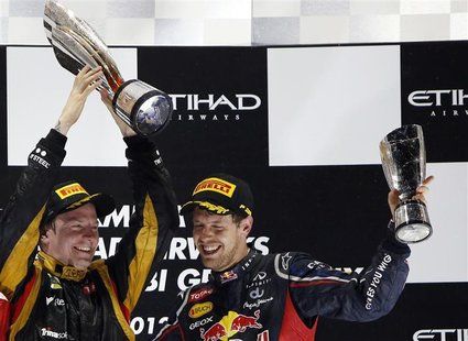 Lotus F1 Formula One driver Kimi Raikkonen of Finland and Red Bull Formula One driver Sebastian Vettel of Germany llift their trophies after