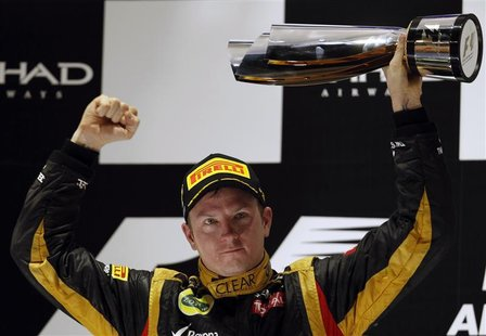 Lotus F1 Formula One driver Kimi Raikkonen of Finland lifts his trophy after winning the Abu Dhabi F1 Grand Prix at the Yas Marina circuit o