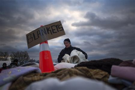 A victim of hurricane Sandy takes blankets from a aid distribution site in the Staten Island borough of New York November 3, 2012. Fuel supplies headed toward disaster zones in the U.S. Northeast on Saturday and a million customers regained electricity as near freezing temperatures threatened to add to the misery of coastal communities devastated by superstorm Sandy. Credit: Reuters/Adrees Latif