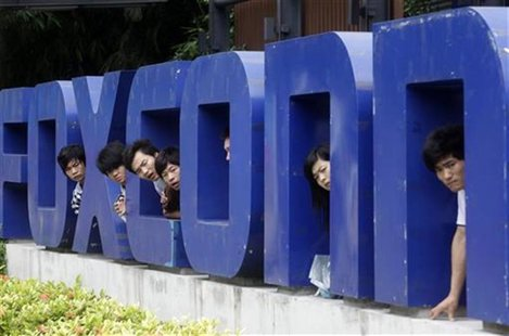 Workers look on from a Foxconn logo near the gate of a Foxconn factory in the township of Longhua, Guangdong province May 29, 2010. REUTERS/