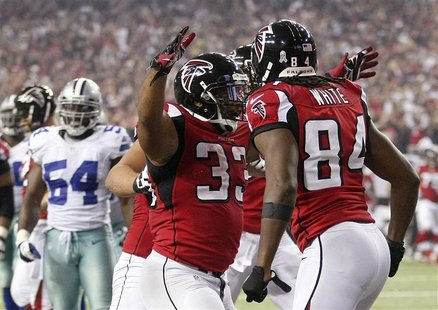 Atlanta Falcons running back Michael Turner (33) celebrates with teammate and wide receiver Roddy White (84) after a touchdown against the D
