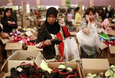 A woman picks a pair of Crocs footwear for her child during its sale at Central Park shopping mall in Jakarta in this August 16, 2011 file p